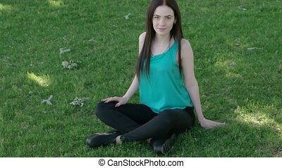 Calm young girl sitting crossed legs on grass