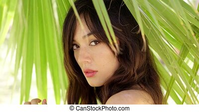 Calm young woman in shade of palm leaves - Single gorgeous...