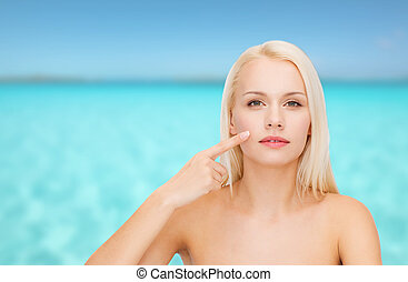 calm young woman pointing at her cheek - health and beauty ...