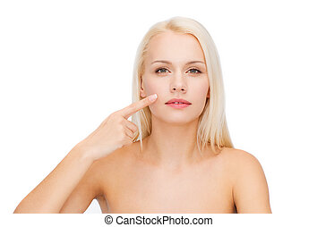 calm young woman pointing at her cheek - health and beauty...