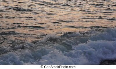 Calming Black sea surf at sunset