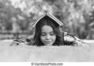 Calming book. Small child sleep on green grass. Bibliotherapy. Mindfulness and relaxation. Napping time. Back to school. Non-formal education and learning. Relaxing book for better sleep.