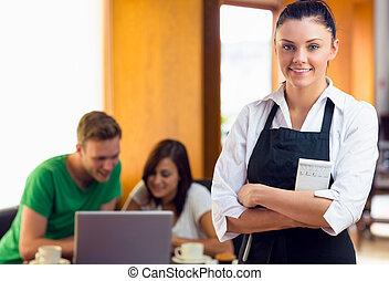 camarera, con, dos, estudiantes, usar la computadora portátil, en, tienda de café