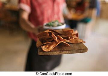 camarero, tenencia, un, tabla porción, de, recientemente, cocido al horno, nachos