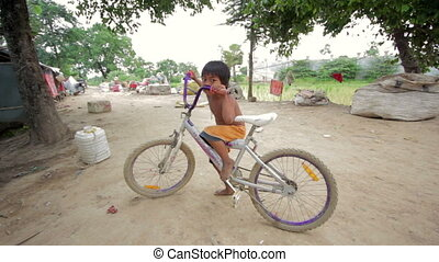 Cambodian boy in slum with bicycle