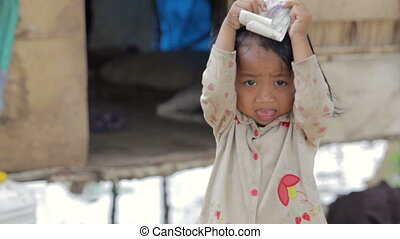 Cambodian kid holding money in slum