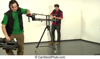 camcorder on crane - two video technical workers disassemble...