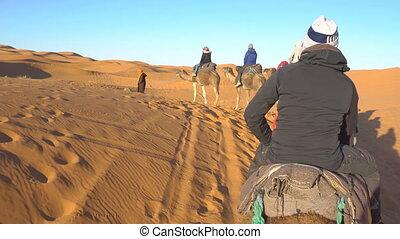 Camel riders are walking through the sand desert in Erg Chebbi desert in Morocco, Africa. Caravan of tourists in the morning desert.
