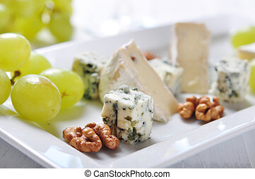 Camembert and blue cheese on plate with grape and walnut ...