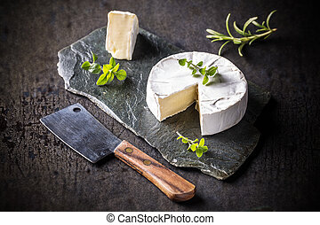 Camembert - French camembert pieces served on slate surface
