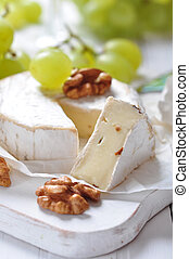Camembert on wooden cutting board with grape and walnut ...