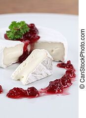 Camembert with cranberry jam and parsley on white plate. ...