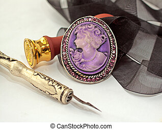 Cameo - Closeup of old cameo, with old pen and golden stamp