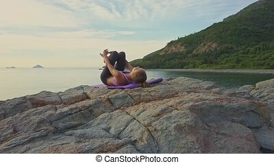 Camera Approaches Girl Holding Yoga Pose against Hilly Beach...