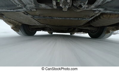 Camera below car while driving on winter road