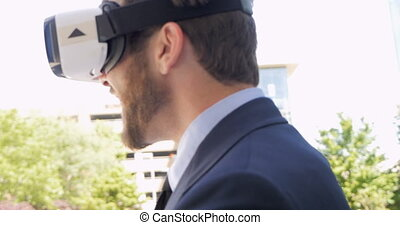 Camera circles a happy businessman wearing a VR headset virtual reality working