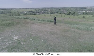 Camera circling around a man standing on the top of a hill and lifting his arms smoothly upwards.