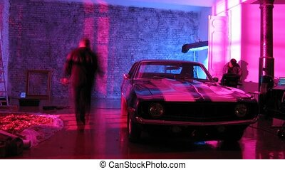 Camera crew videotape nice car in front of wall while...