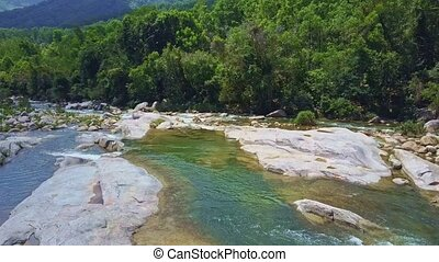 Camera Flies over Clear River with Huge White Stones