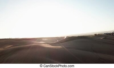 Camera flies to the sun in a sand desert, wonderful nature landscape with sand dunes and sunset. Woman is wilking in a desert landscape. Gran Canaria