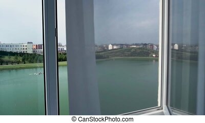 Camera flight through an open window with a view of the lake outside the window.