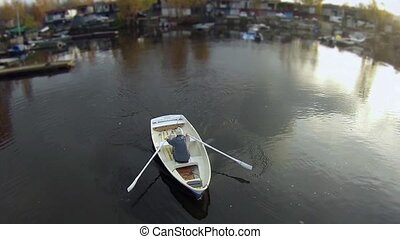 camera flying over the rowing boat - man in a rowing boat ...
