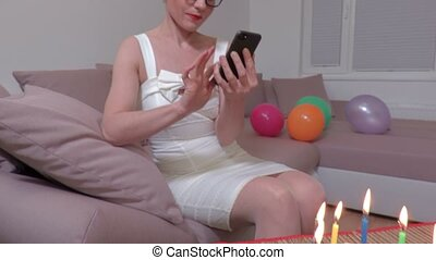 Camera focuses on birthday cake with candles then on woman who using smart phone