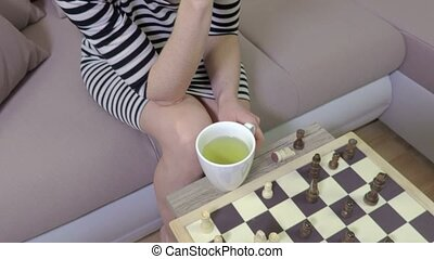 Camera focuses on chessboard then on woman chess player