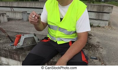 Camera focuses on smoking construction worker