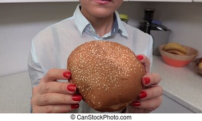 Camera focuses on the burger then on the woman who is starting to eat