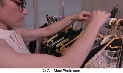 Camera focusing on woman's hands near the rack