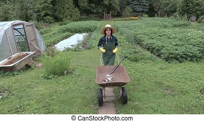 Camera follow woman gardener with wheelbarrow