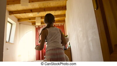 Camera following a cute little girl with her soft toy running through the house