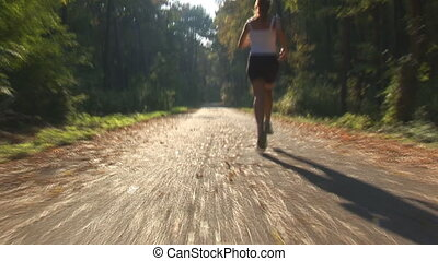 camera following speedy running woman on street through forest