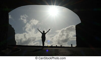Camera follows a woman silhouette walking out from tunnel towards the sunlight. Burst of bright light. Raising arms in air.