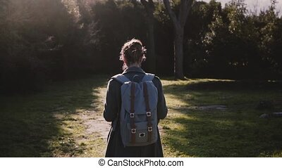 Camera follows beautiful girl with backpack and map exploring ancient summer sunny forest road in Ostia slow motion.