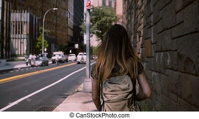 Camera follows European brunette woman with long flying hair walking along big red brick building wall, slow motion.