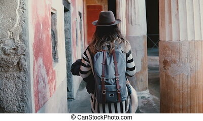 Camera follows excited female tourist with backpack and map exploring amazing ancient open air museum in Pompeii, Italy.