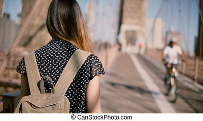 Camera follows female tourist with backpack and dark golden...