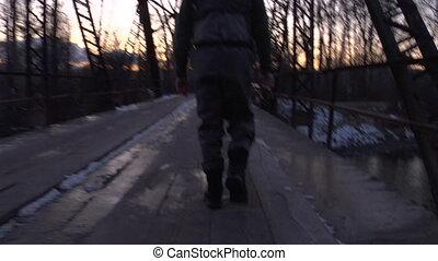 camera follows fly fisherman walking across bridge in winter