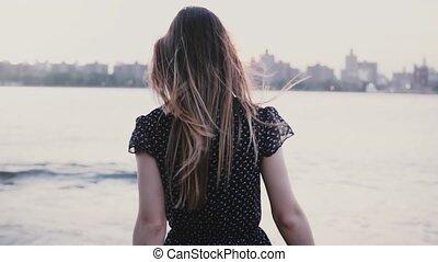 Camera follows girl in black dress run down to big river...