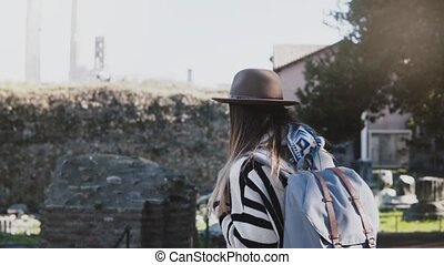Camera follows happy casual European girl with backpack...