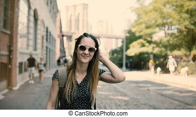Camera follows happy excited European tourist girl with backpack and camera in sunglasses smiling, turning around 4K.