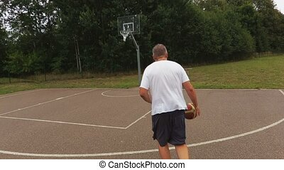 Camera follows the basketball player who try to throw in basket
