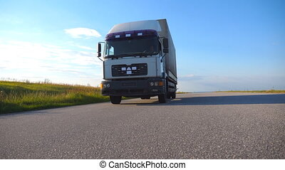 Camera follows to truck driving on a highway. Lorry rides...