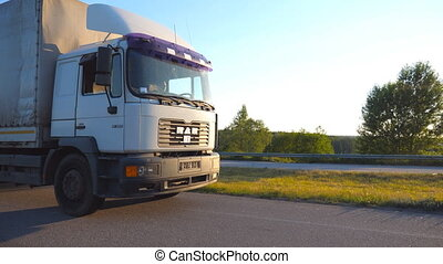 Camera follows to truck driving on highway in evening. Lorry rides through countryside with sunset at background. Driver is driving at high speed. Close up of truck cab. Side view Slow motion