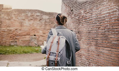 Camera follows young excited traveler woman with backpack...