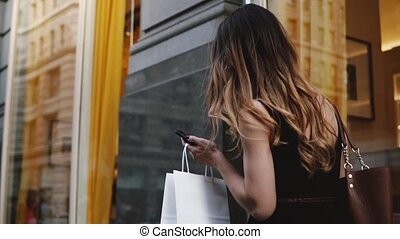 Camera follows young female beauty blogger carrying shopping...