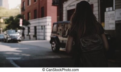 Camera follows young female tourist with backpack crossing...