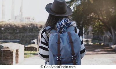 Camera follows young female tourist with backpack enjoying beautiful ruins of the Forum in Rome during vacation travel.